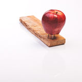 Apple nailed to a piece of wood Royalty Free Stock Image