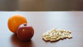 Apple, naranja y píldoras rojos en la tabla Imágenes de archivo libres de regalías