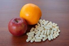 Apple, naranja y píldoras rojos en la tabla Foto de archivo libre de regalías