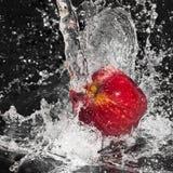 Apple nel flusso continuo dell'acqua della spruzzata sul nero immagine stock libera da diritti