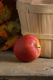 Apple next to wood basket Stock Photography