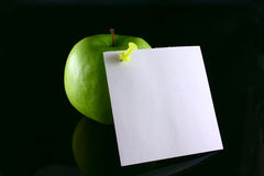 Apple on a note. Green apple with the pinned sheet of paper, removed on the blacked out glass Royalty Free Stock Image