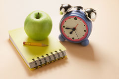 Apple, Notebook and Alarm Clock Stock Photo