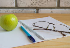 Apple, notebook, reading glasses and pen on wooden table. Back to school concept Royalty Free Stock Image