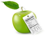 An apple with a nutrition facts label. Stock Photos
