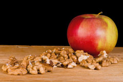 Apple and nuts. We can see an apple and nuts in this photo. This is a still life Stock Images
