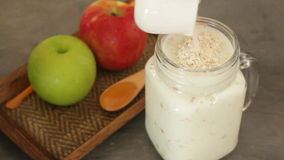 Apple with oats and honey smoothie in small jar stock video