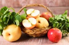Apple och asiat i korg på wood bakgrund Royaltyfri Foto