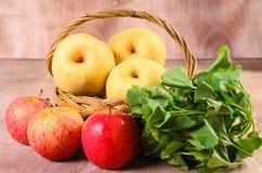 Apple och asiat i korg på wood bakgrund Royaltyfria Bilder