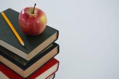 Apple och blyertspenna på bokbunt Fotografering för Bildbyråer