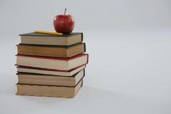 Apple och blyertspenna på bokbunt Royaltyfri Bild
