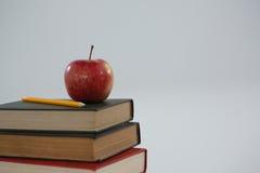 Apple och blyertspenna på bokbunt Royaltyfria Bilder