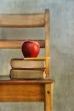 Apple och gammala böcker på skolastol Arkivbilder