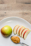 Apple och jordnötsmör i platta Arkivfoto