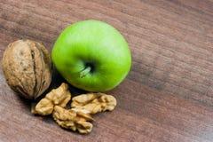 Apple och valnötter på trä Arkivfoton
