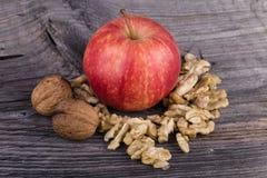 Apple och valnötter på träbakgrund Arkivbild