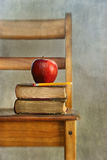 Apple and old books on school chair. With vintage feel Stock Images