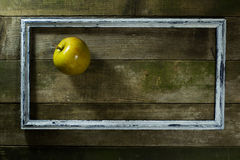 Apple in the old frame. On a wooden background royalty free stock photos
