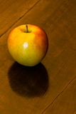 Apple on an Old Table. Studio shot of an apple on an old wooden table. Healthy and delicious Stock Image