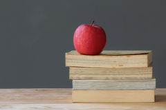 Apple on the old textbook Stock Photography
