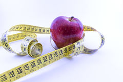 Apple and one centimeter. Red apple and an inch around Royalty Free Stock Images