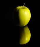 Apple op weerspiegelende grond Stock Foto's