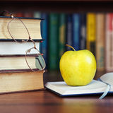 Apple on the open book Stock Images