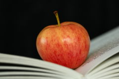 Apple and open book Stock Images