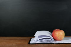 Apple And Opened Book With Blackboard Background On The Wooden Desk