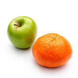 Apple and orange. A green apple and a mandarin orange on a white background Stock Image