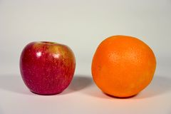Apple and Orange. An apple next to an orange.Illustrates the popular phrase: Comparing apples to oranges Stock Images