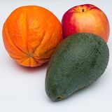 Apple, orange and an avocado on white background stock photography
