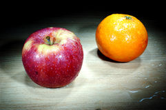 Apple and orange in the dark Stock Photo