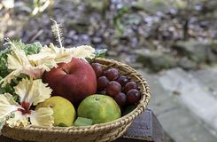 Apple, Orange and grape in weave bamboo baskets with floral decorations Background blurry trees stock photo