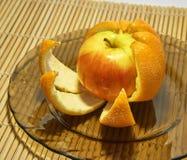 Apple in orange peel Stock Photography