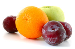 Apple, orange and plums. Apple, orange and  three lilac  plums on overwhite background Royalty Free Stock Photography