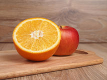 Apple and orange. Orange and red ripe apple on a wooden cutting board Stock Photos