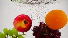 Apple, Orange und Trauben, die in Wasser mit Blasen in der Zeitlupe fallen Frucht auf weißem Hintergrund stock video footage