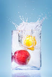 Apple and orange in water splashes Royalty Free Stock Photography