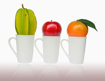 Apple, Orenge και Carambola που τίθενται στο φλυτζάνι Στοκ Εικόνες