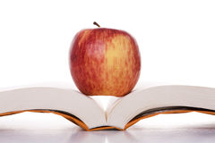 Apple over a open book Stock Photography