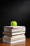 Apple over pile of books Stock Photos