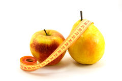 Apple, päron och linjal Arkivbild