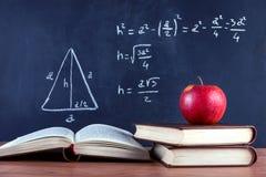 Apple på böcker och svart tavla med Pythagoreanteorem arkivbild
