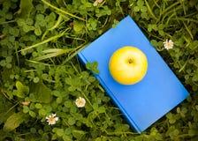 Apple på boken på gräs Utbildningsbegrepp, tillbaka till skolan Arkivfoto