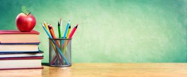 Apple på bunt av böcker med blyertspennor och den tomma svart tavlan Arkivbild