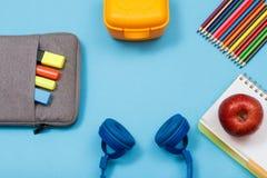 Apple på den öppna skrivboken, färgblyertspennor, lunchask, hörlurar, påse-blyertspenna fall på blå bakgrund arkivbild