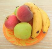Apple, pêssego e banana na placa alaranjada foto de stock royalty free