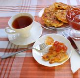 Apple pancakes with a cup of tea. Apple fritters with jam and tea on a checkered cloth Stock Photos
