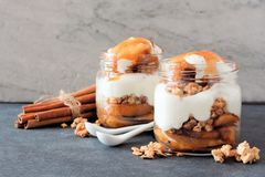 Apple parfaits with caramel in mason jars on a stone background Royalty Free Stock Photos